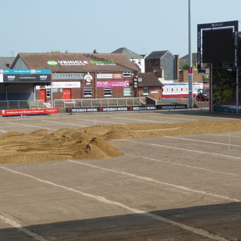 Sand is dumped along the length of the pitch area.