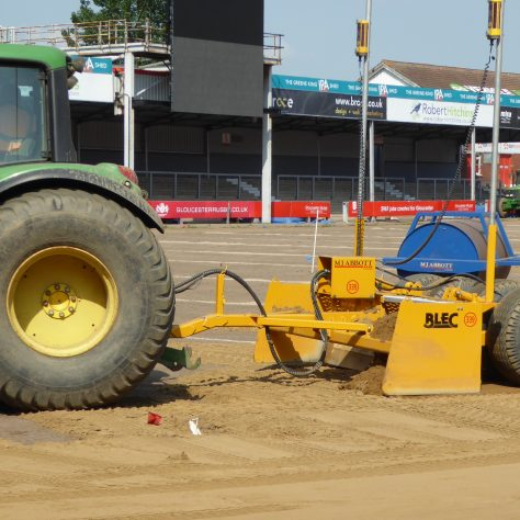 A close up showing the sand being shifted to the appropriate level.