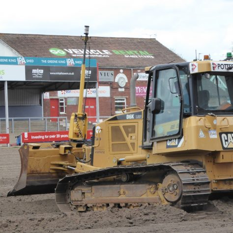 The bulldozer travelling across the pitch to start a new run.