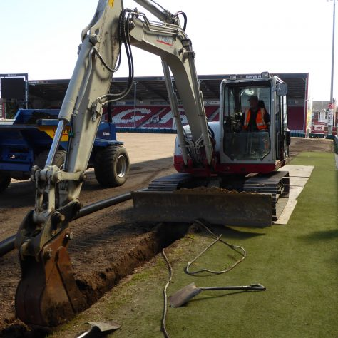 Excavating the main drainage trench.   Evidence of old floodlighting cable on the ground.