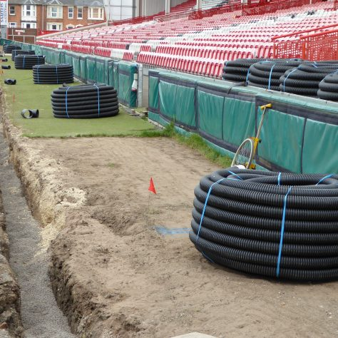 Coils of 100mm drainage pipe ready to be installed across the width of the pitch.