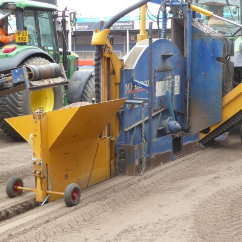 The hopper dispensing gravel into the trench containing the drainage pipe.