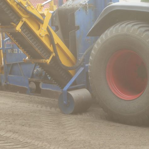 Amidst the dust a roller smoothes out the tractor tyre marks.