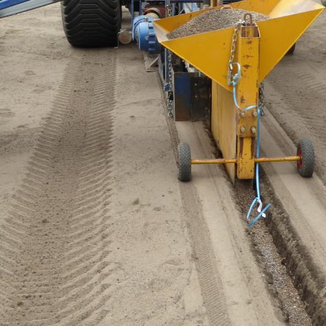 A close up of the hopper filling up the trench with gravel.