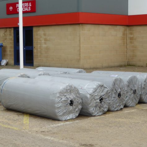 38 2m wide rolls of mat, approximately 100m long, have been stored in the corner of the main carpark.  The view shows some of the rolls covered in protective plastic.