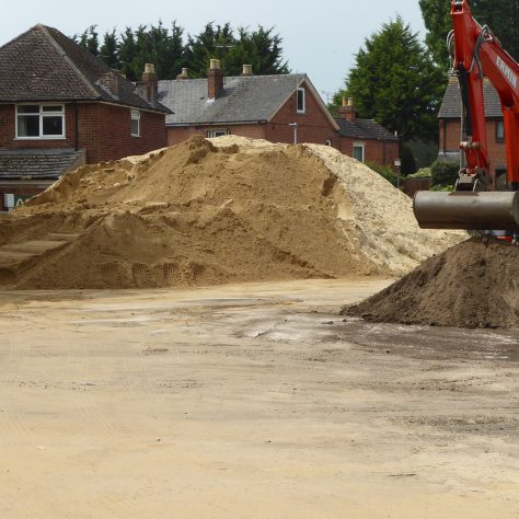 The pile of sand is reducing but it will take several more days to get it all onto the new pitch.