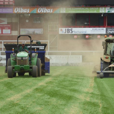 On the left - laying more sand.  On the right brushing and raking the sand.   The effect of the rake can clearly be seen.