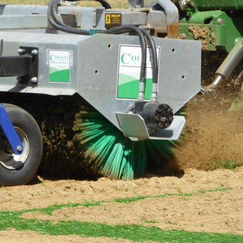 The brush rotates anti-clockwise lifting the fibres and spreading the sand.