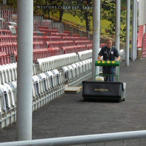 No, he's not mowing the walkway.  The mower has been fitted with brushes to clean the surface of the new tarmac.