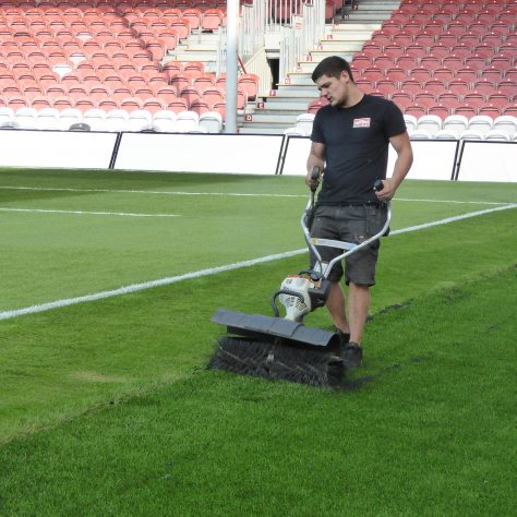 Brushing up the join between the Astroturf and the edge of the pitch in front of the South stand.