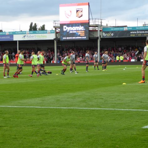 The players finally take to the pitch for their warm-up before the first match on the new pitch.