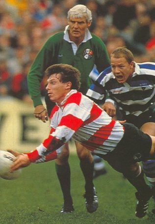 Cup semi-final 1989: Hannaford passes the ball out. Referee Roger Quittenton and Richard Hill of Bath look on.